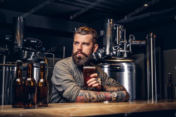 Tätowierte Hipster Männchen mit stilvollem Bart und Haar trinken Bier sitzen an der Bar Theke