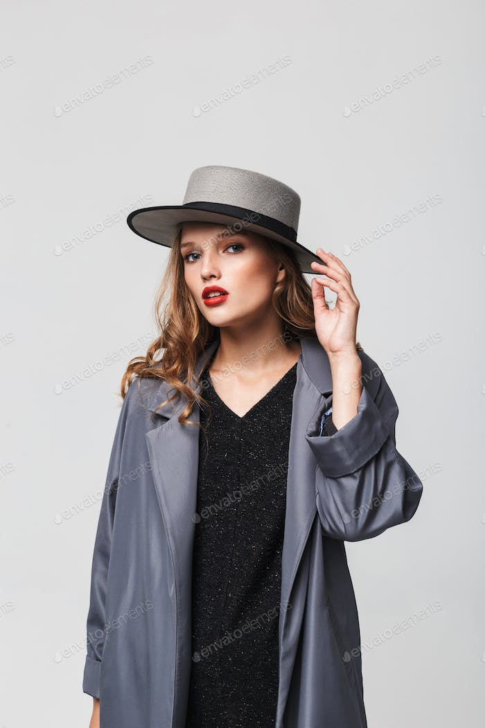 Young attractive woman with wavy hair in hat and cloak thoughtfully looking in camera