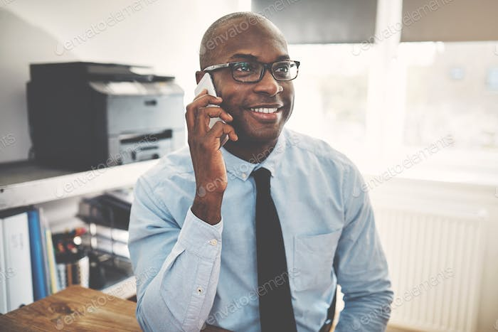 Smiling African businessman talking on a cellphone in an office