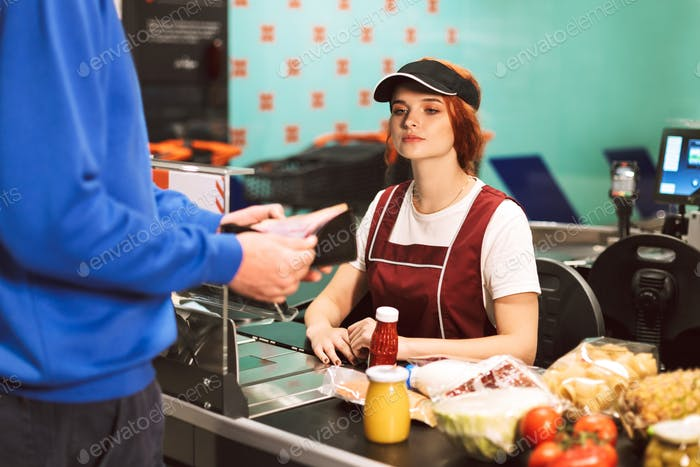 Young female cashier in uniform thoughtfully looking at customer