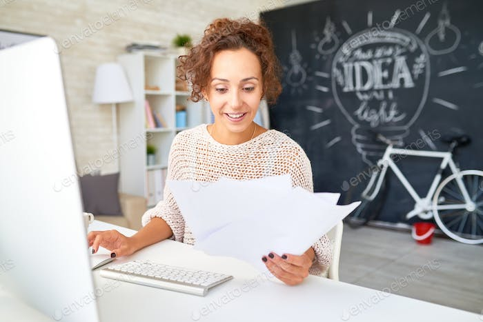Happy Young Woman Reading Business Documents at Desk