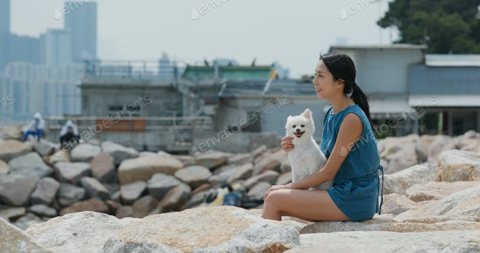 Woman hug with her pomeranian dog and sit at seaside