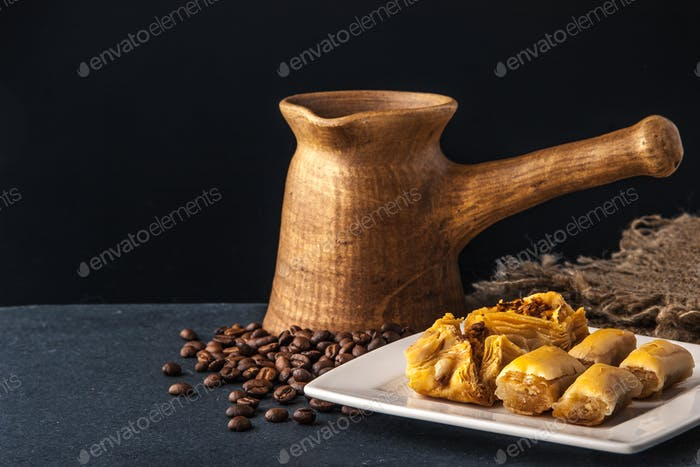 Wooden cezve with baklava on the dark table horizontal