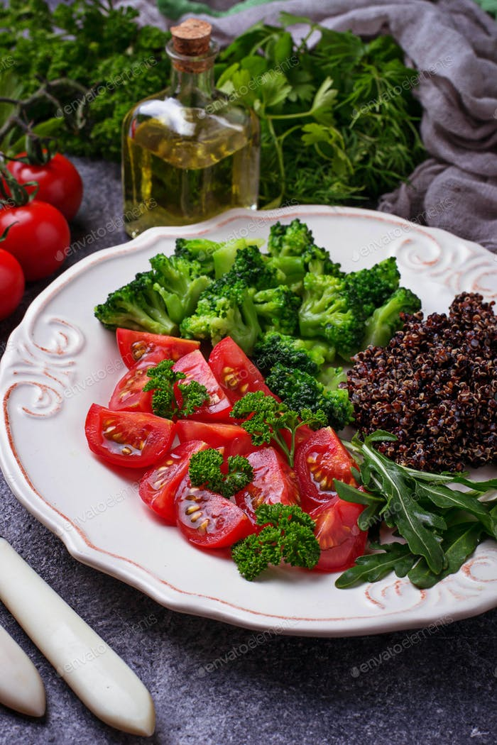 Salad with black quinoa, cherry tomatoes, broccoli and arugula