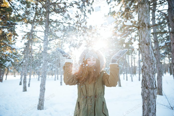 Cheerful happy woman having fun with snow in winter park