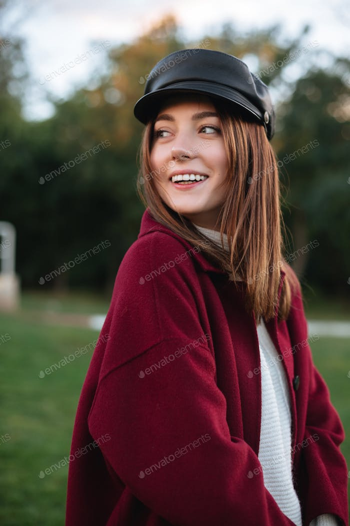 Beautiful girl in black cap and coat standing in park and joyfully looking aside