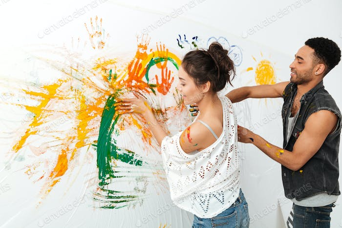 Couple painting on white wall by hands and colorful paints