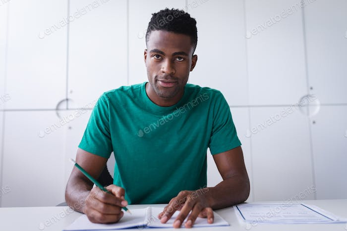 Happy african americen businessman sitting at desk while having a video call making notes