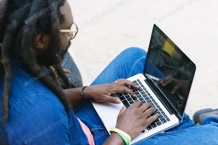Retrato do homem africano sentado lá fora com laptop.