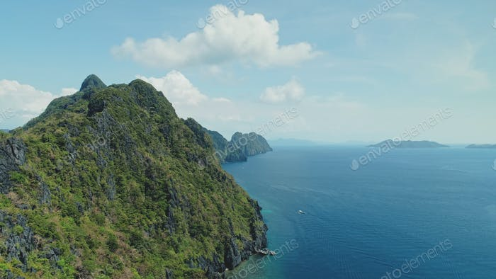 Mountainous island landscape with green tropic jungle forest. Asia seascape of ocean bay