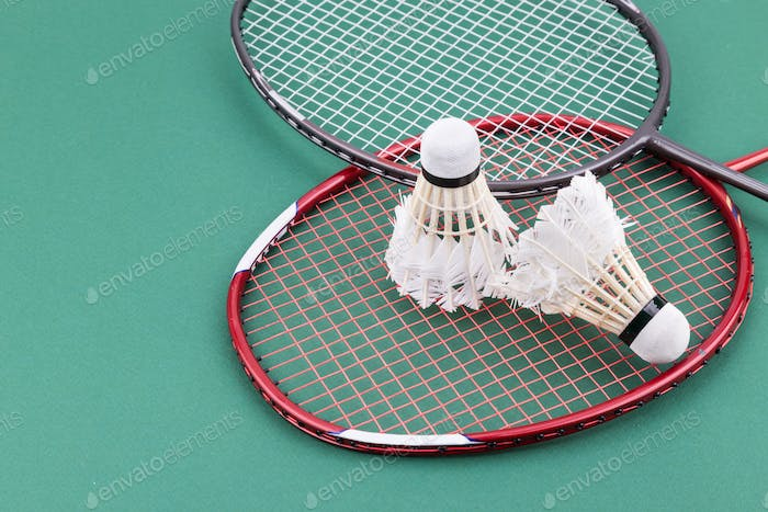 Two worned out badminton shuttlecock with racket on green court