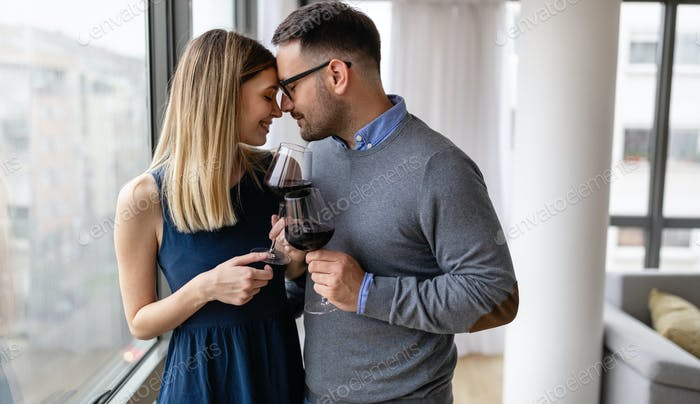 Valentine's day, birthday, celebration concept. Romantic happy couple in love drinking wine at