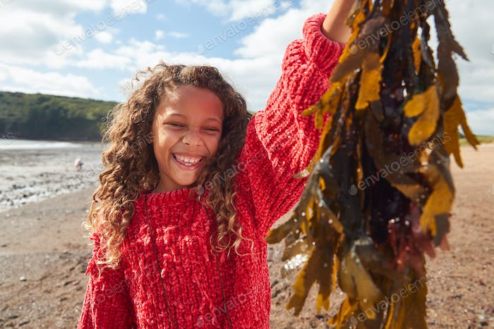 Portrait Of Smiling Girl Holding Seaweed On Winter Beach Vacation