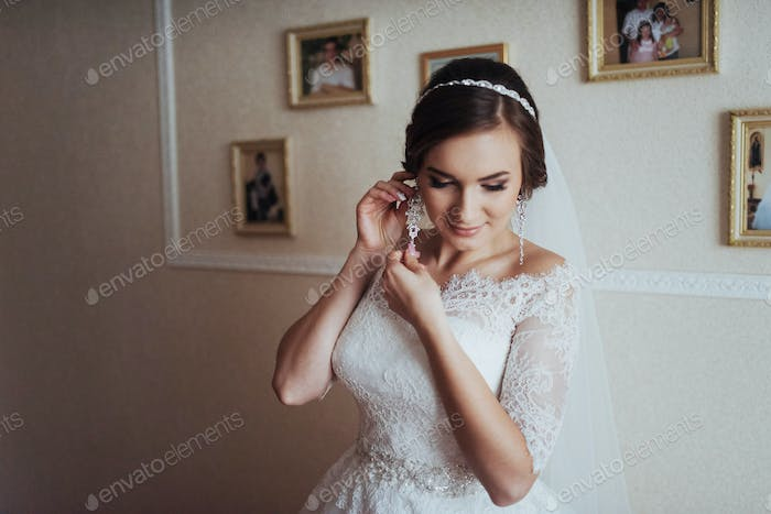 Wedding day. Beautiful bride trying on earrings