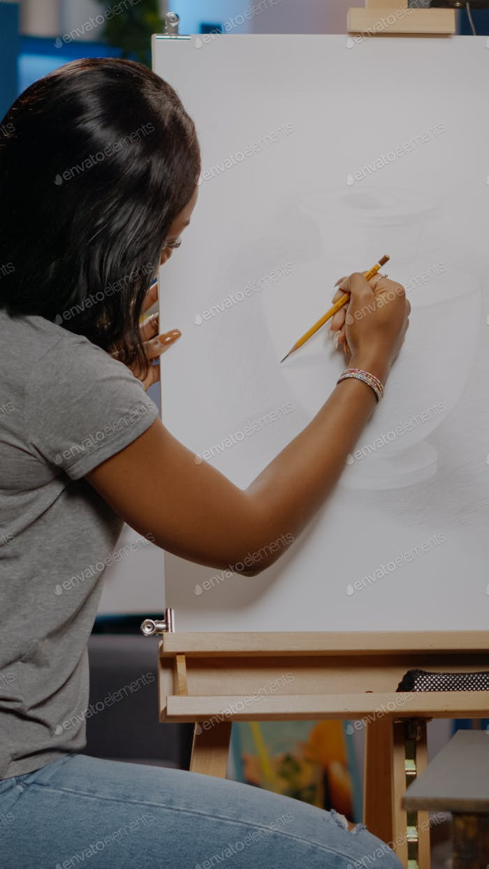 Woman of african american ethnicity drawing vase