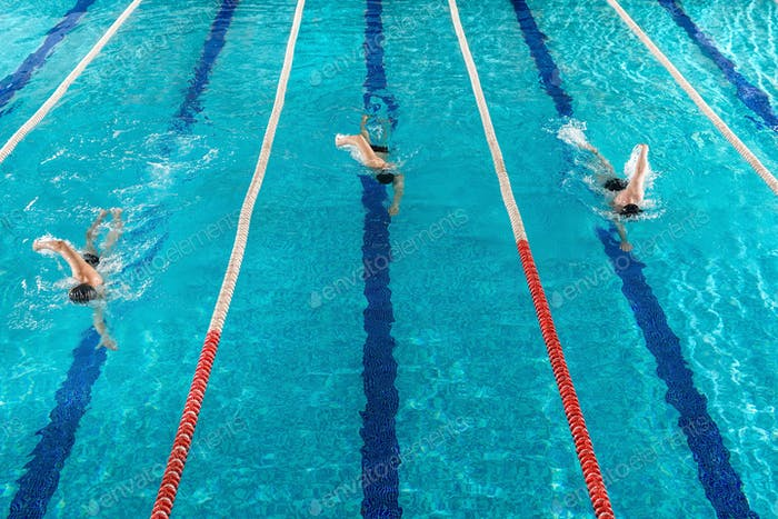 Three male swimmers racing against each other