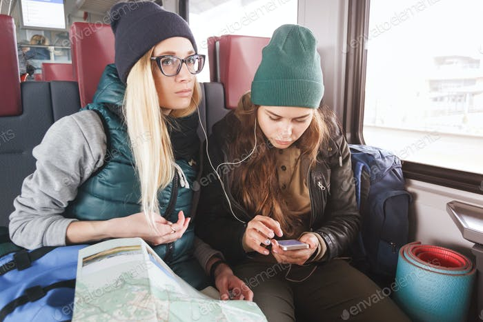 Two young women travelers with backpacks and map in the train