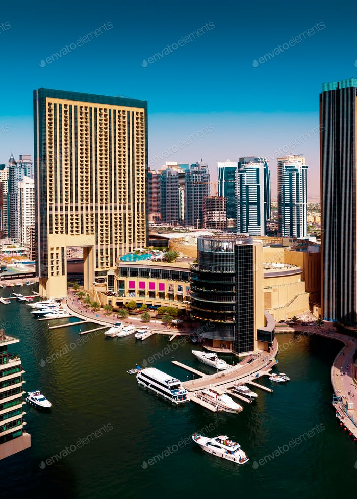 Colorful dubai marina skyline with water canal during sunny day, Dubai, United Arab Emirates.