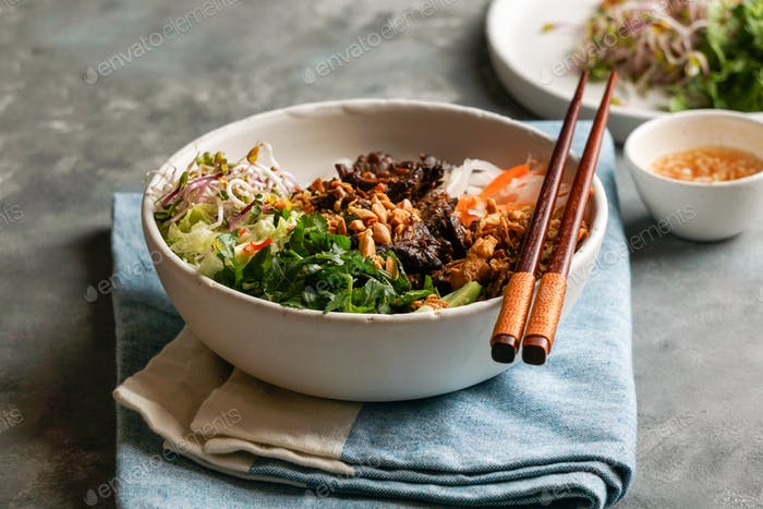 bowl of traditional Vietnamese noodle salad - Bun Bo Nam Bo, with beef, pickled vegetables sauce