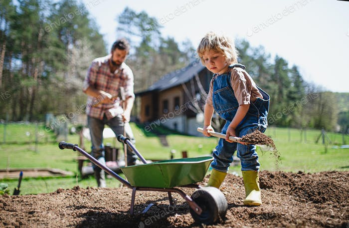 Father with small son working outdoors in garden, sustainable lifestyle concept