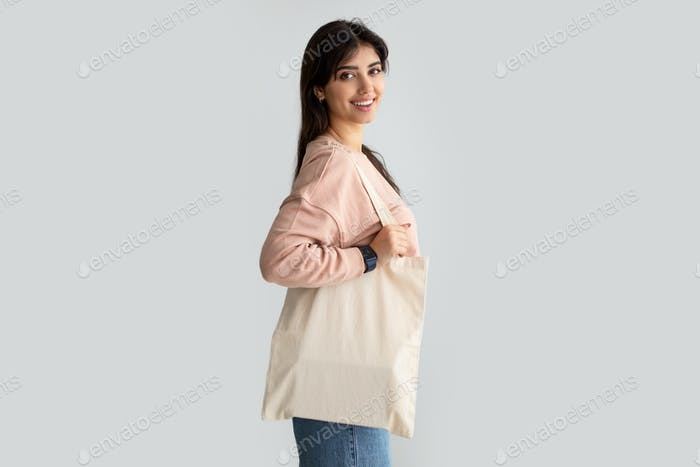 Portrait of young woman standing with blank canvas tote bag