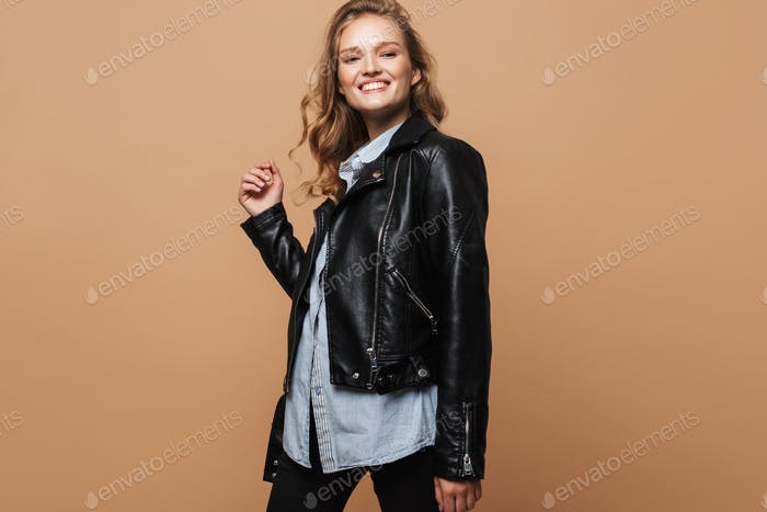 Young cheerful lady with wavy hair in black leather jacket and shirt happily looking in camera