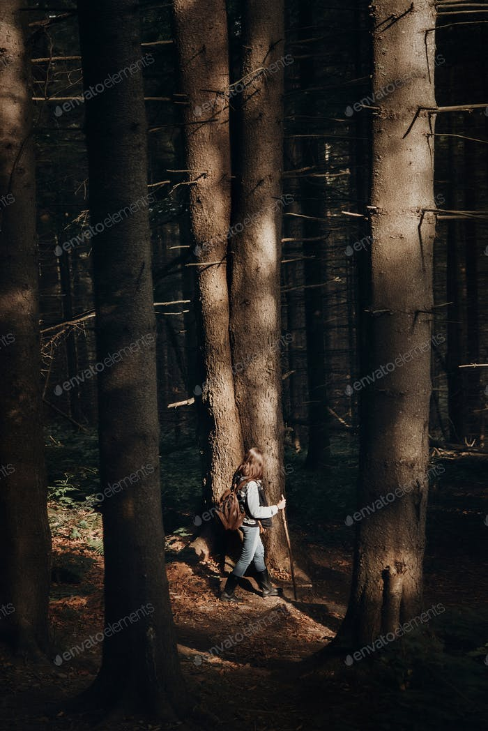 hipster traveling with backpack, walking in woods in light