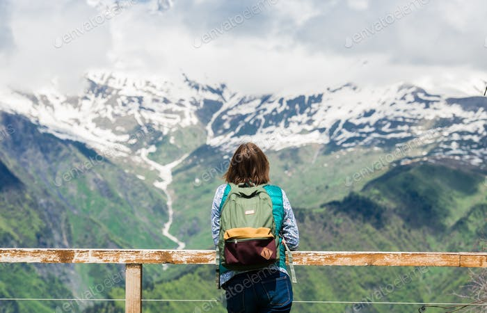 Young woman is standing at viewpoint and looking beautiful mountain landscape. Hiking female tourist