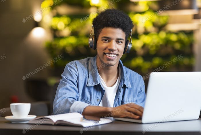 Cheerful teen guy with headset working with laptop
