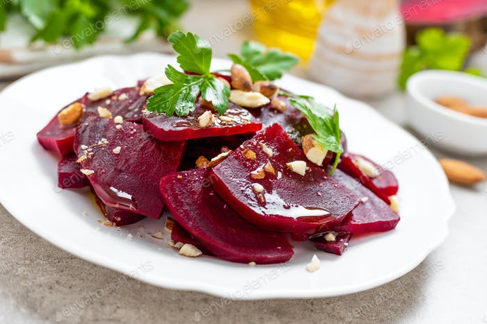 Vegetarian salad with boiled beet, almond nuts and oil. Healthy food