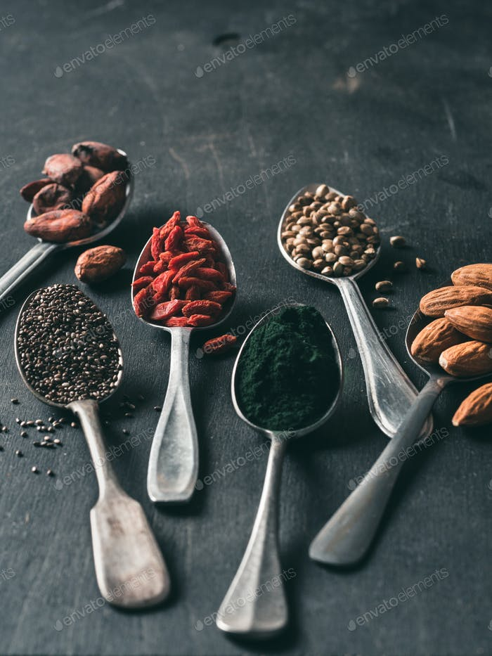 Spoons of various superfoods on black wooden table