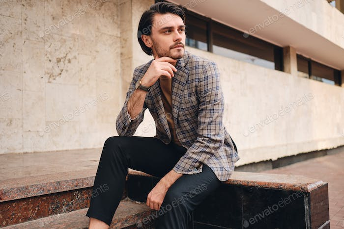 Young attractive stylish man in checkered jacket confidently looking away outdoor
