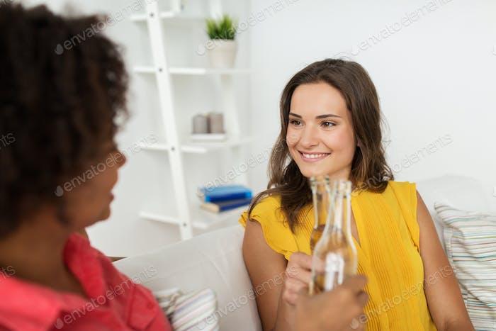femmes heureuses clinking bouteilles de bière à la maison