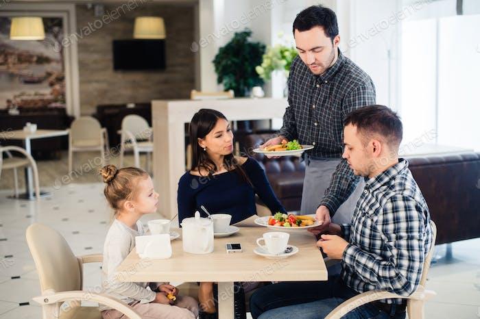 Happy family having breakfast at a restaurant