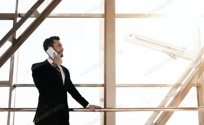 Cheerful businessman standing in airport, talking on phone