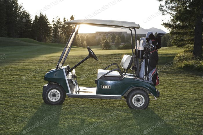 A golf cart with bags sitting on a golf course.