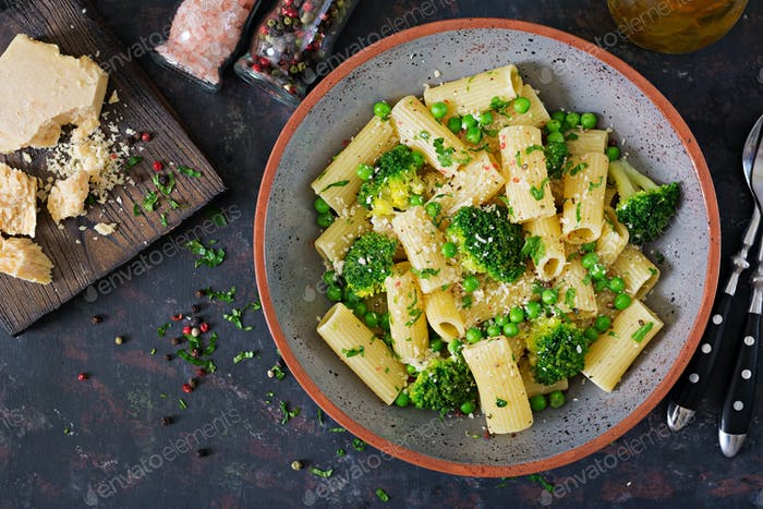 Pasta rigatoni with broccoli and green peas. Vegan menu. Dietary food. Flat lay. Top view.
