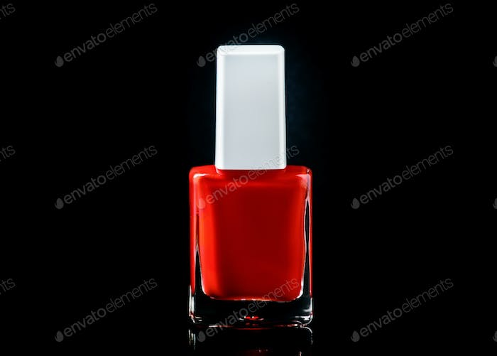 Red nail polish in bottle on glossy black background