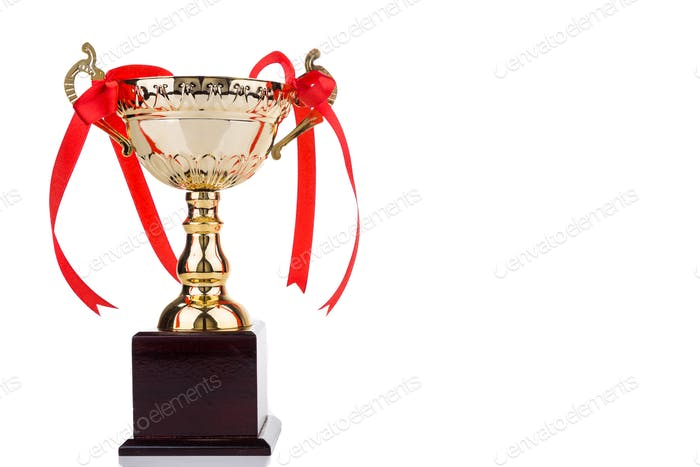 Gold trophy with red decorative ribbons on wooden table