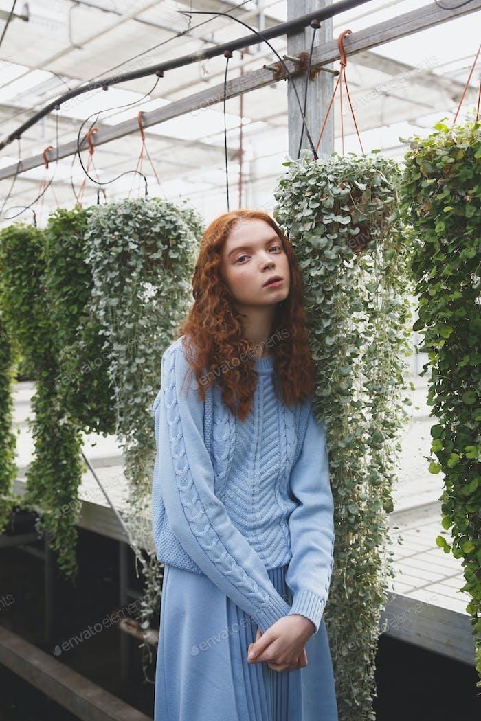 Girl standing near climbing plants