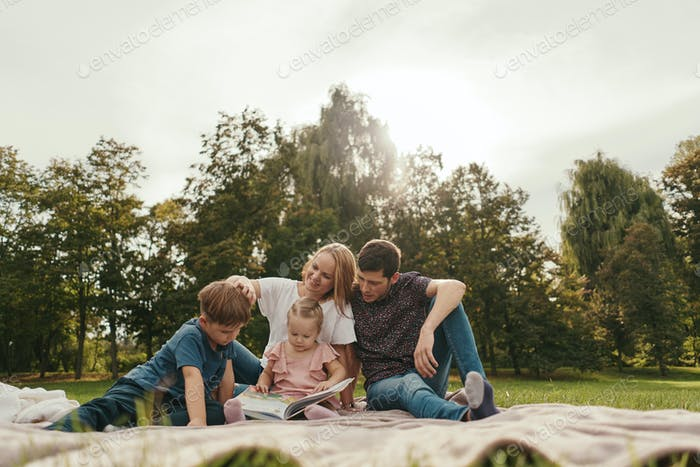 Happy family spends time together reading a book in the park