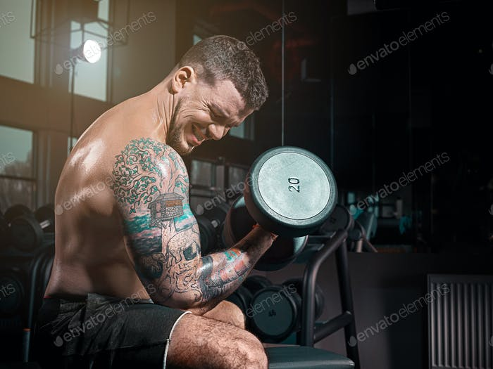 Very power athletic guy bodybuilder , execute exercise with dumbbells, in dark gy,