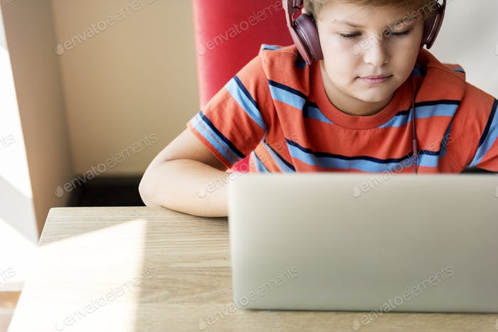Kid Boy Headphone Using Laptop Concept
