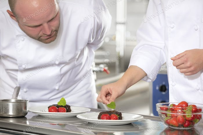 Professional chefs decorate dessert cake with lemon leaf