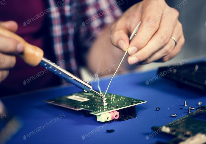 Hands soldering tin on electronics circuit board