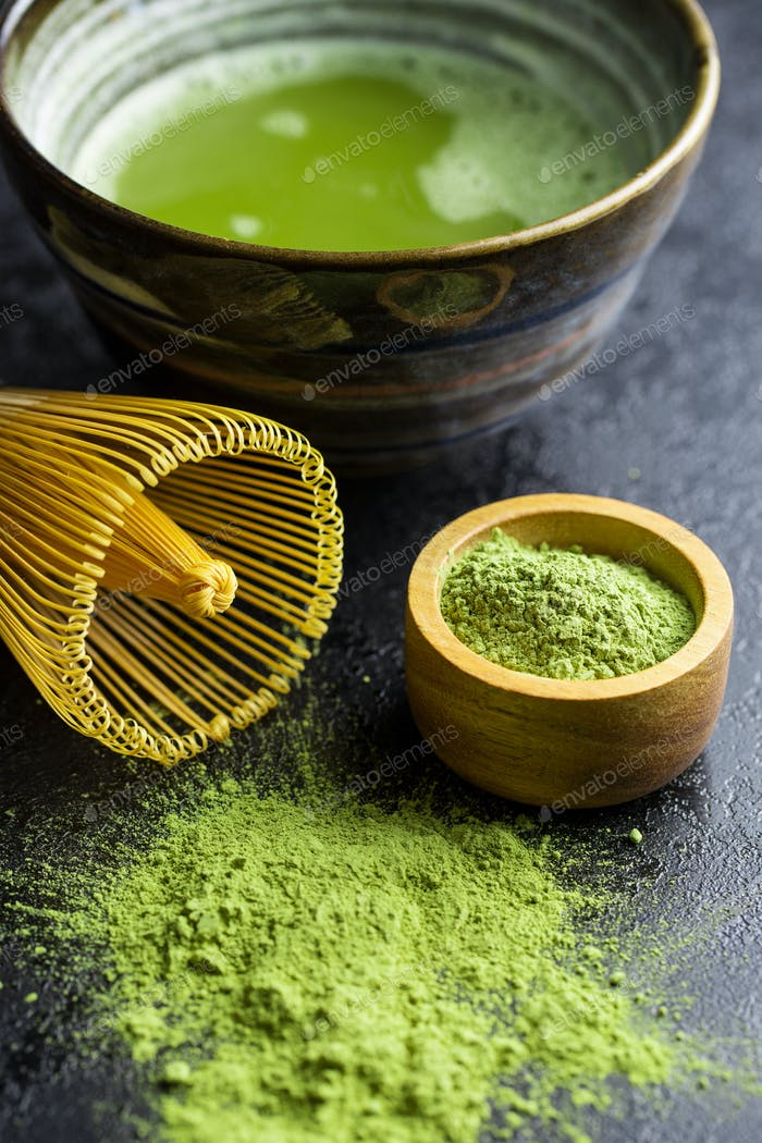 Green matcha tea powder with bamboo whisk , spoon and bowl.