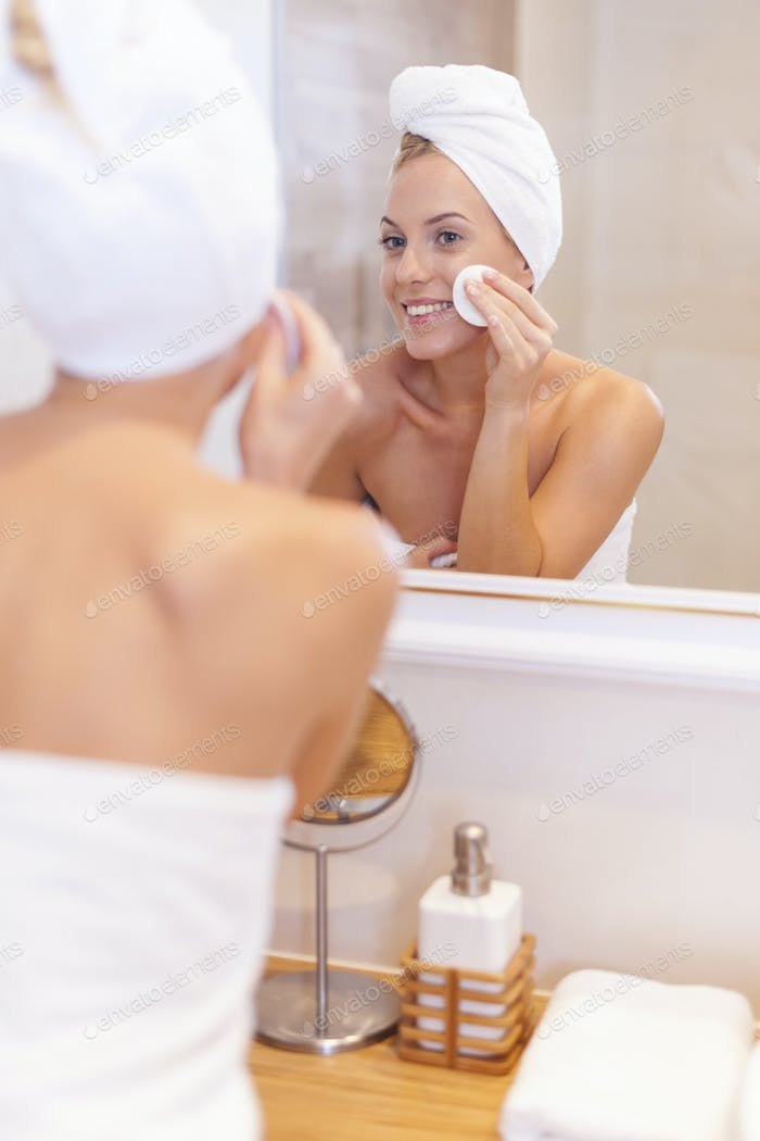 Woman cleaning face in front of mirror