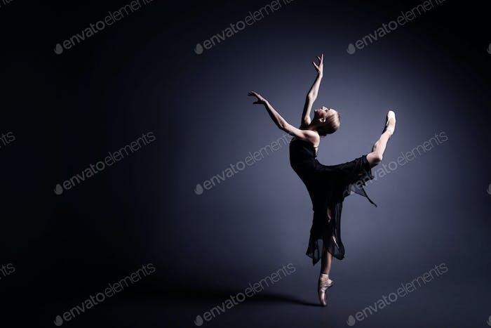 Young ballerina in a black suit is dancing in dark studio