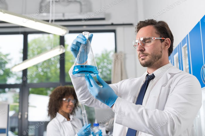 Serious Scientist Looking At Flask With Blue Liquid In Laboratory Over Group Of Scientific
