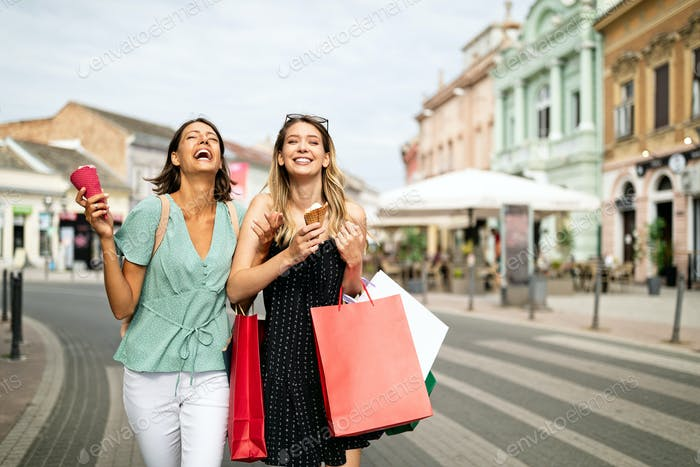 Sale and tourism, happy people concept. Beautiful women friends with shopping bags in the ctiy